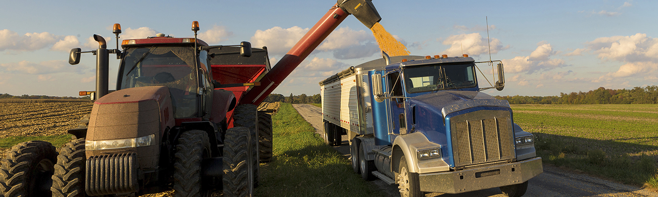 A red tractor and grain cart unloading grain into a blue semi-truck