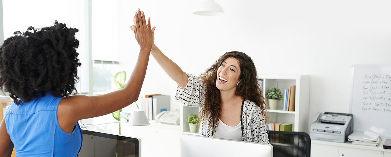 Two ladies high five in an office.