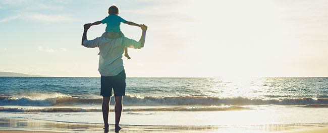 A child on his father's shoulders looking at the ocean on a beach.