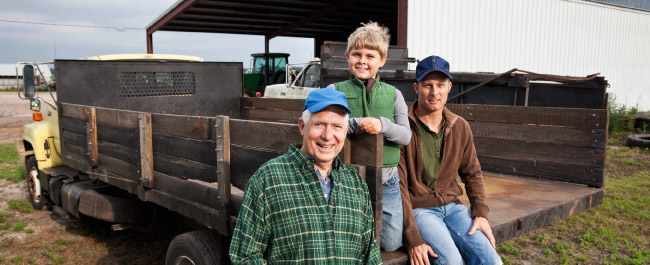 Three generations of farmers sitting/leaning on an old truck in front of a barn.