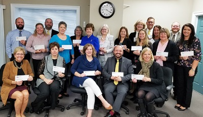 Branch Managers with checks in hand to donate to several local, non-profit organizations in honor of Giving Tuesday