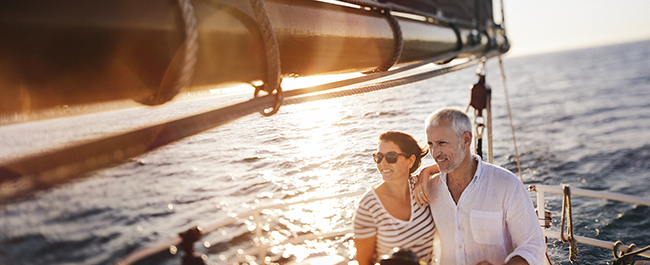Middle-aged couple sailing near sunset