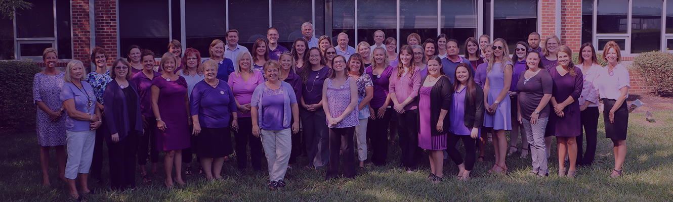 Employees wearing purple stand together to show their support for the fight against substance abuse