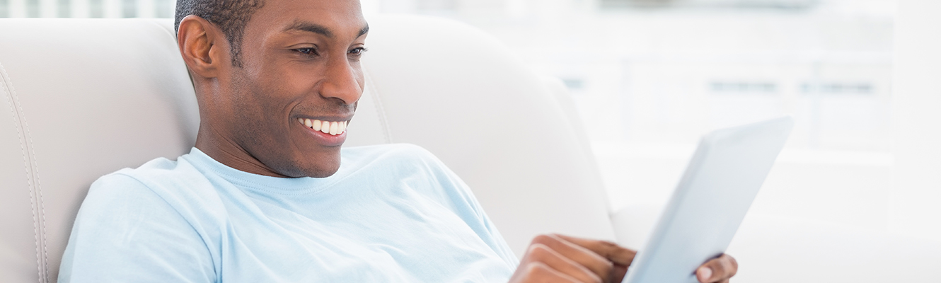 African American Male Smiling While Using IPad