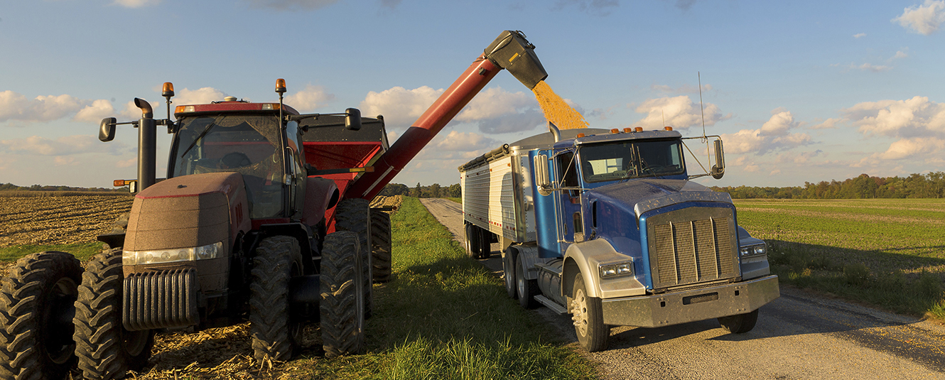 A tractor and grain cart unloading grad into a semi truck