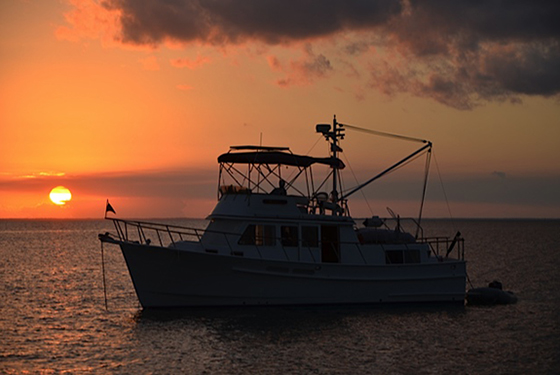 A 36 ft Monk Trawler achnored at sunset off Guana Cay Abaco Bahamas