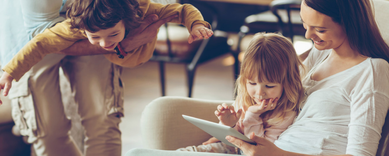 A father and son playing airplane while the mother and daughter are looking at a tablet.