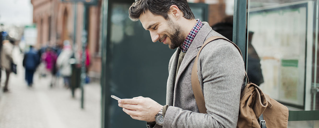 A man looking at his smart phone and smiling while on the side of a street
