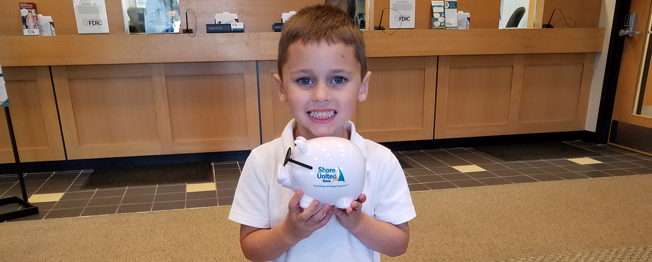 A young boy inside a Shore United Bank branch with a piggy bank that has Shore United Bank's logo on it.