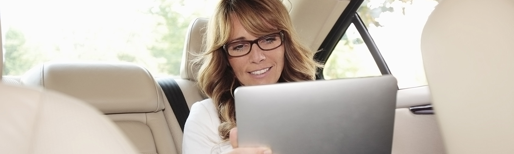 woman in backseat of car on tablet