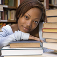 An African American student leaning her head on books