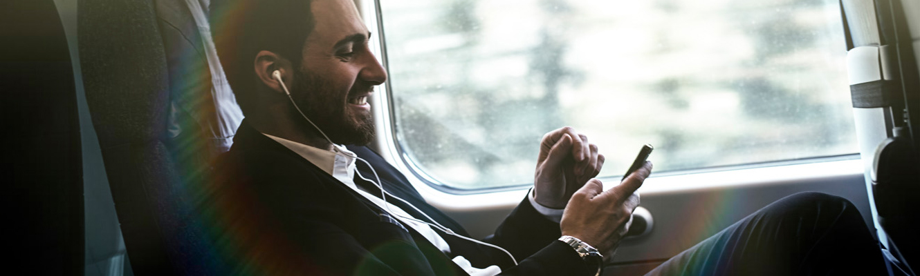 man traveling on train listening music on phone with earbuds