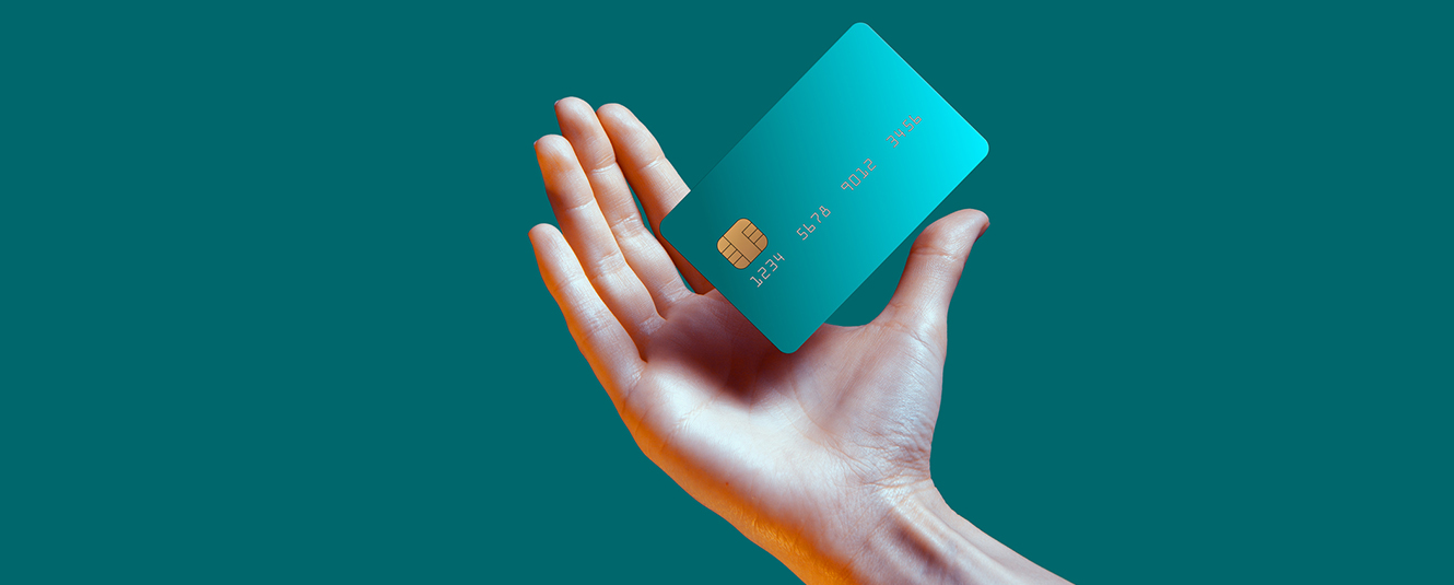 a person's hand holding a debit card