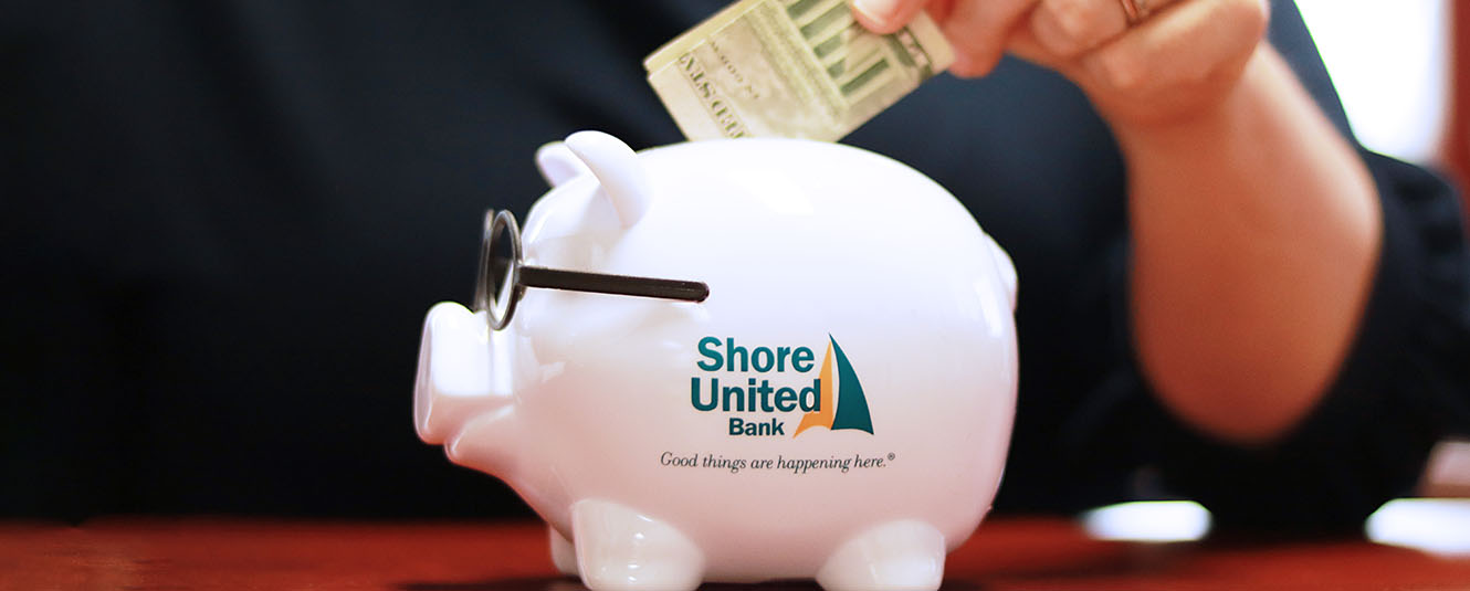 A lady wearing a navy blue shirt putting money into a Shore United Bank piggy bank.