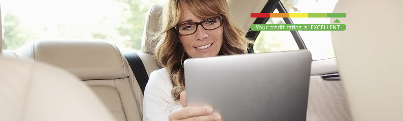 A woman in the backseat of a car with an ipad and a credit score rating